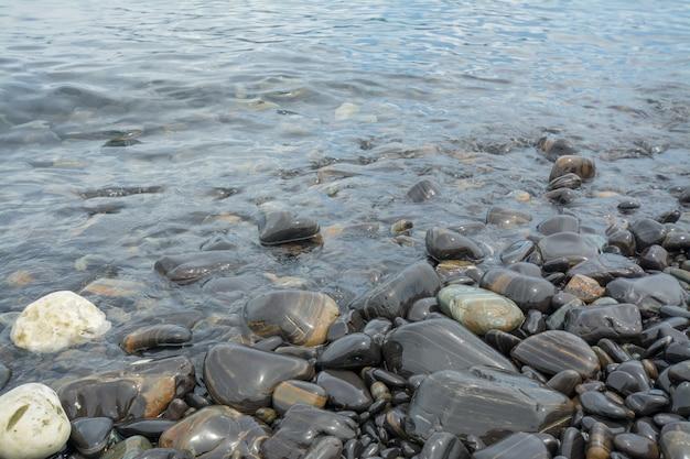 背景として黒い石のビーチ、黒い石の海岸。