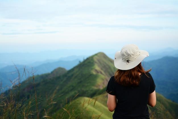若い女の子がカメラに背を向けて、山と青空の背景の景色を楽しんでいます。
