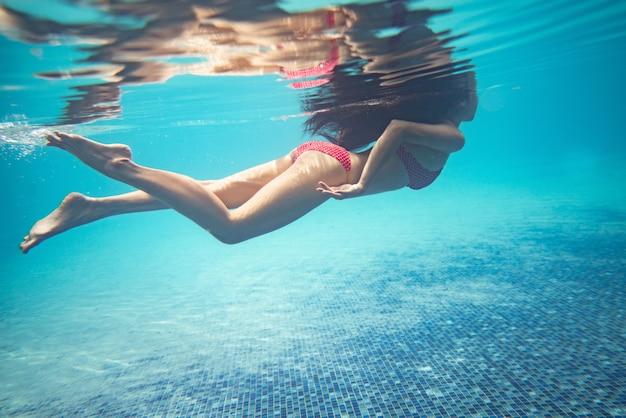 アジアの女性はプールでダイビングしています。