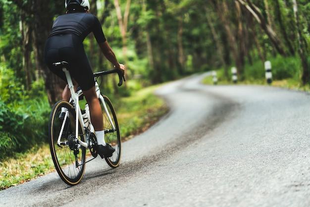 サイクリスト彼は森の中を登りながら上り坂をサイクリングしていました。