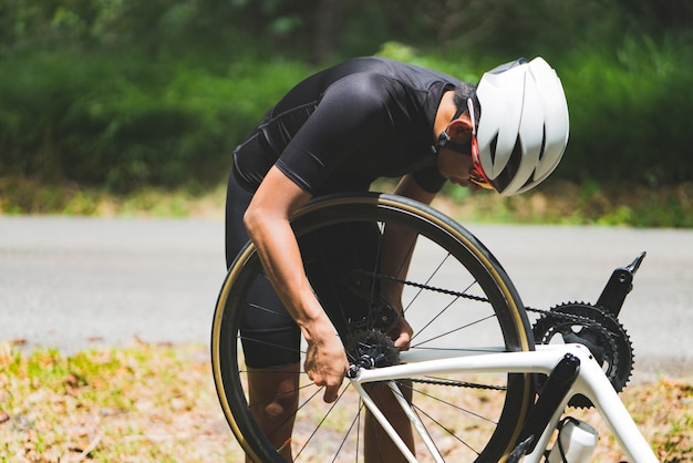 Велосипедист ремонтирует велосипед на дороге, у него протекает резина.