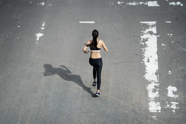 道路を走るフィットネス女性