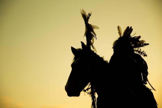 Силуэт индийского человека на лошади на закате