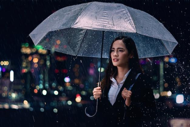 雨の下で傘を持つ女性実業家