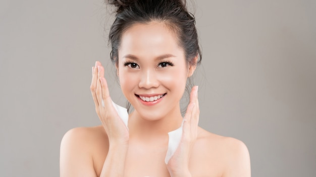 アジアの女性は、顔の泡を使って化粧品を顔から洗い流します