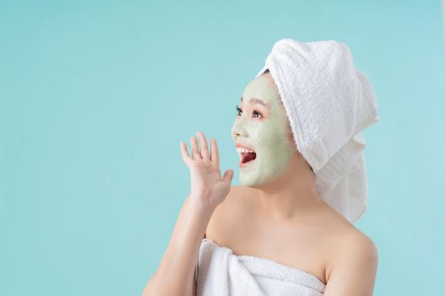 Азиатская женщина это маски для лица. она счастлива и удивлена.