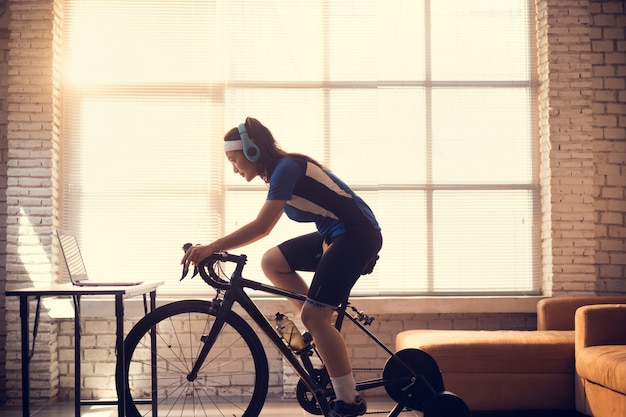 Азиатская женщина велосипедист. она занимается спортом в доме. катаюсь на велосипеде на тренажере и играю в велосипедные игры онлайн.