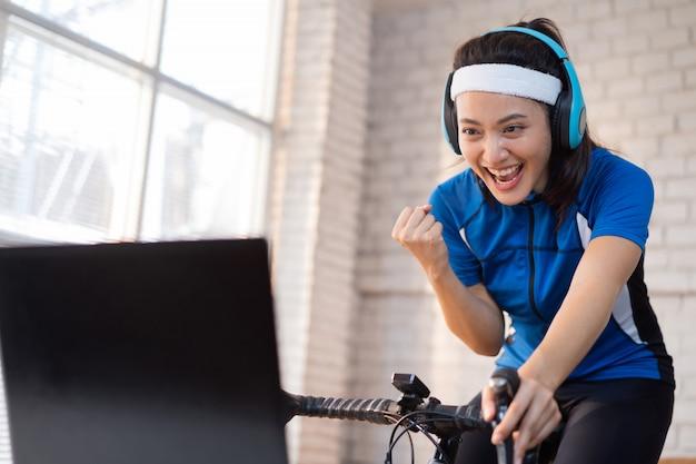 Азиатская женщина велосипедист. она тренируется в доме. катаясь на велосипеде на тренажере и играя в онлайн игры на велосипеде, она довольна