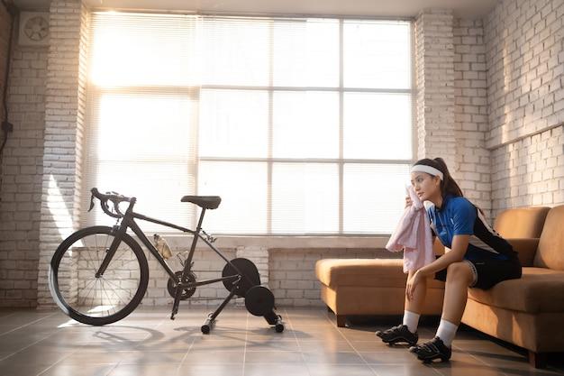 Азиатская женщина велосипедист. она тренируется в доме. катаясь на велосипеде на тренажере и играя в онлайн игры на велосипеде, она ломает