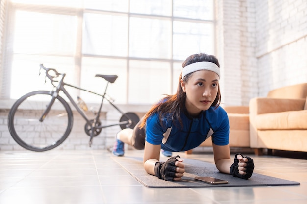 家の中で彼女の板のポーズで運動するサイクリスト