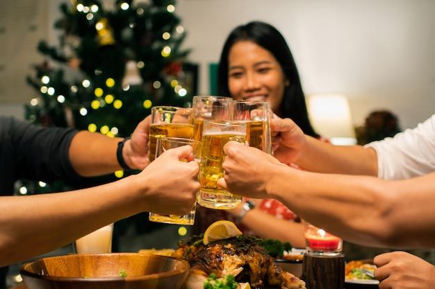 アジアの人々のグループは、自宅でディナーパーティーとビールを持っています。彼らはビールのグラスをチャリンという音します。
