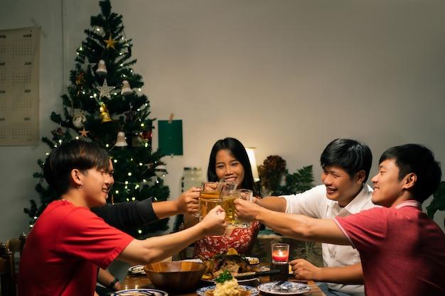 アジアのグループが夕方に家でダイニングとビールをパーティーしています。