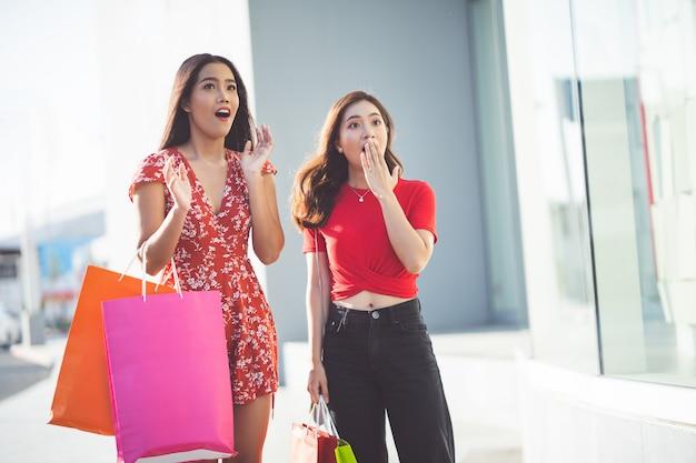 Азиатская женщина друг они делают покупки в торговом центре.
