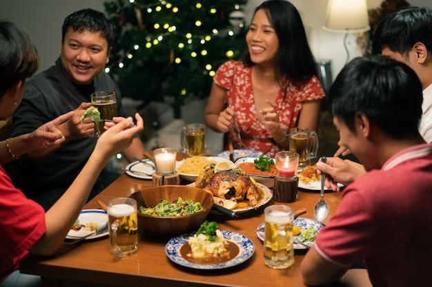 アジアの人々のグループは自宅でディナーパーティーとビールを持っています