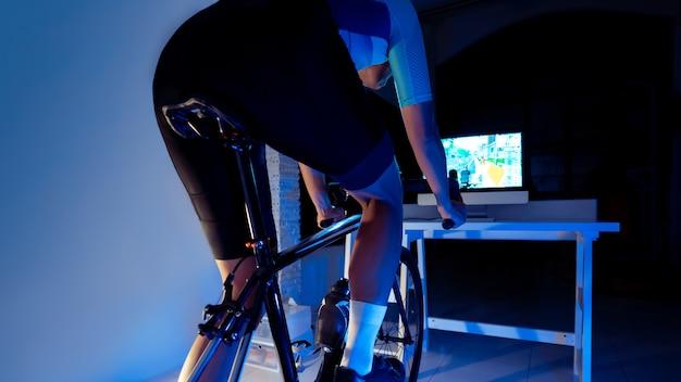 アジア人男性が夜に家でエクササイズしているマシントレーナーでサイクリングしています。彼はオンラインバイクゲームをプレイしています。