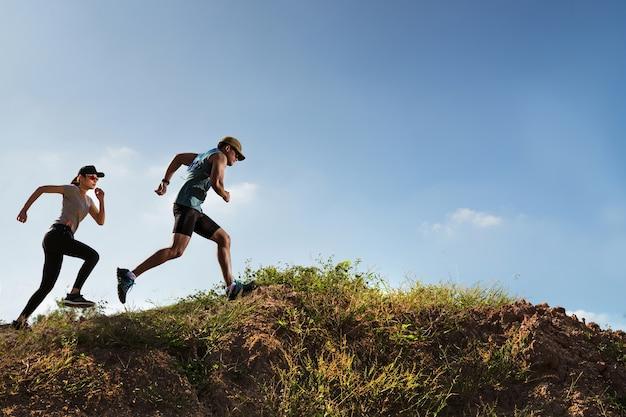 山を走っている男女のトレイルランナー