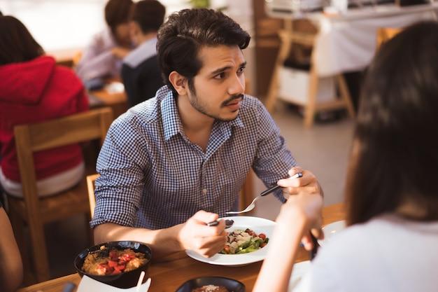 アジアの男性は朝、レストランで友人と食事をしています。