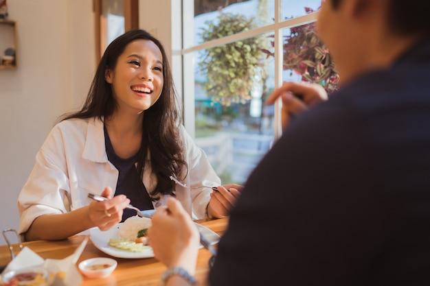 アジアの女性は朝にレストランで食べています。