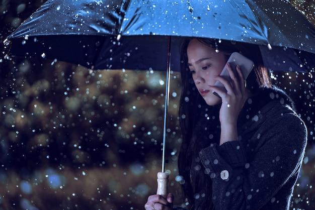 Азиатские женщины используют зонтики, дождь падает. она звонит
