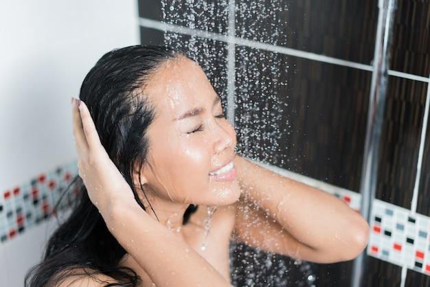 アジアの女性はトイレでシャワーを浴びています。彼女は石鹸をこすりながら、彼女は幸せでリラックスしています。