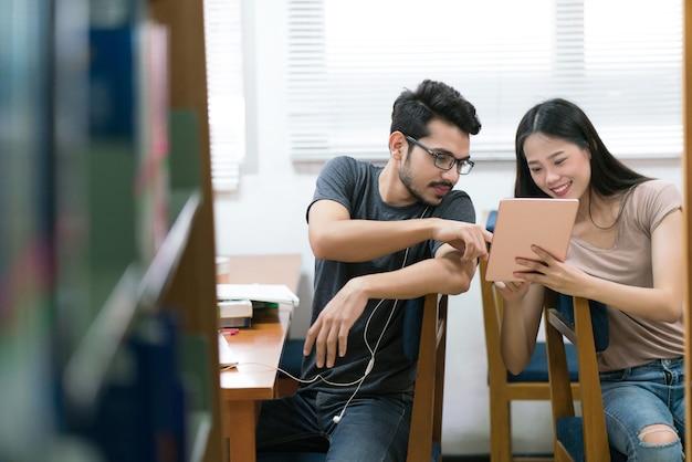 Азиатские студенты помогают друг другу изучать планшетные знания в библиотеке