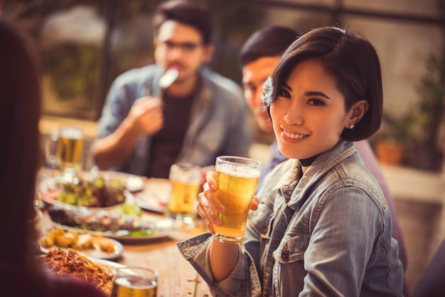 Женщины пьют пиво и очки клинка в ресторане