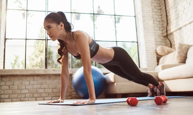 アジアの女性は彼女が行動している家庭で室内で運動する