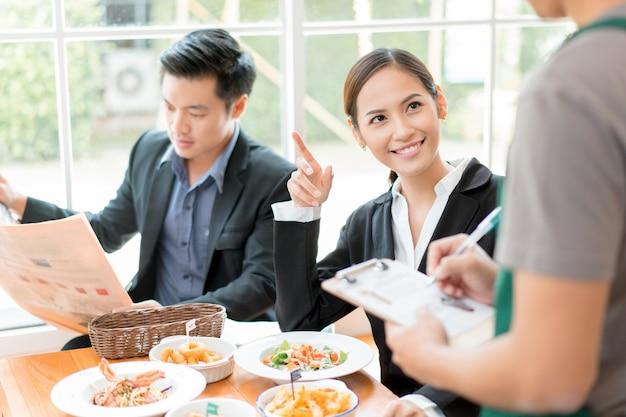 アジアのビジネスマンはレストランで昼食をとって休憩中です。彼女はウェイターから食べ物を注文していました