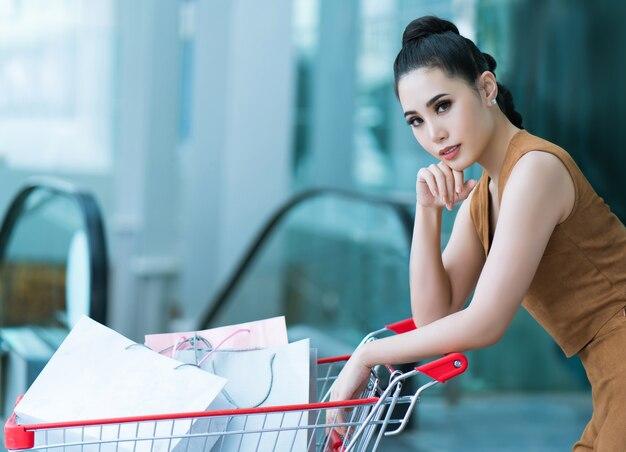 彼女はスーパーマーケットを使用しているアジアの女の子ショッピングモールからカート