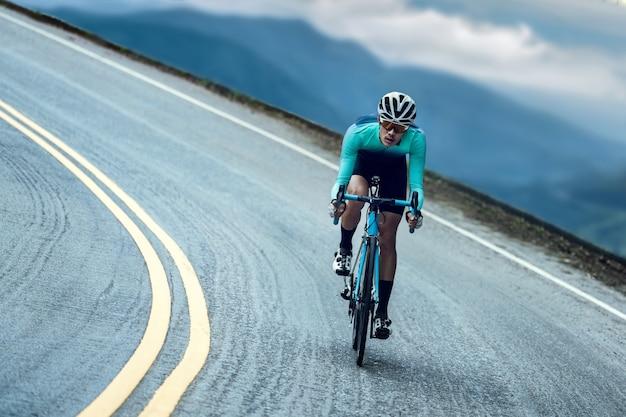 サイクリストはサイクリングをして、トップに登ります。