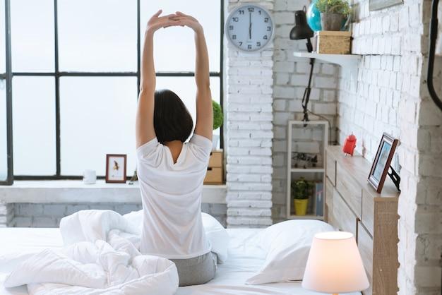 Азиатские женщины она лежит в постели и просыпается утром. она чувствовала себя очень освеженной.