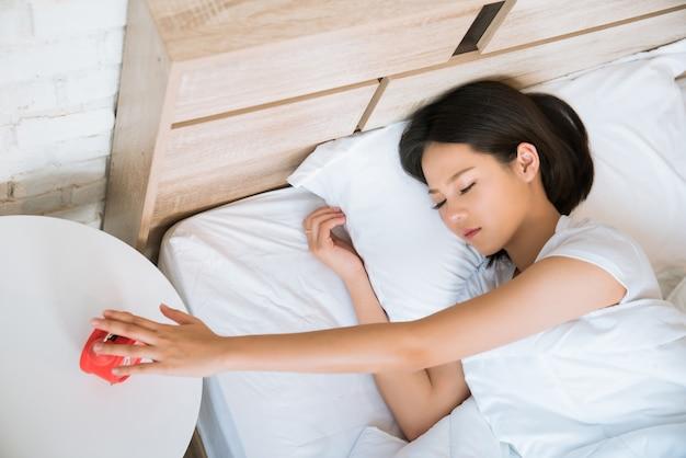 アジアの女性たち目覚め時計を押す彼女が眠っている間