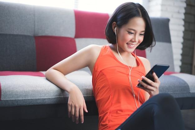 アジアの女の子は自宅で歌の練習を聞いています。