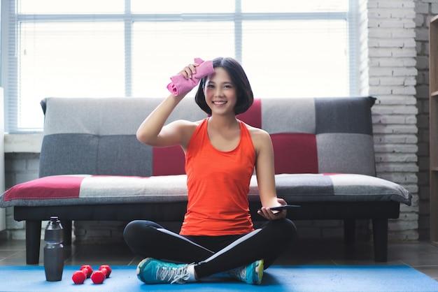 アジアの女性が自宅で運動をした後彼女の汗を拭きます。