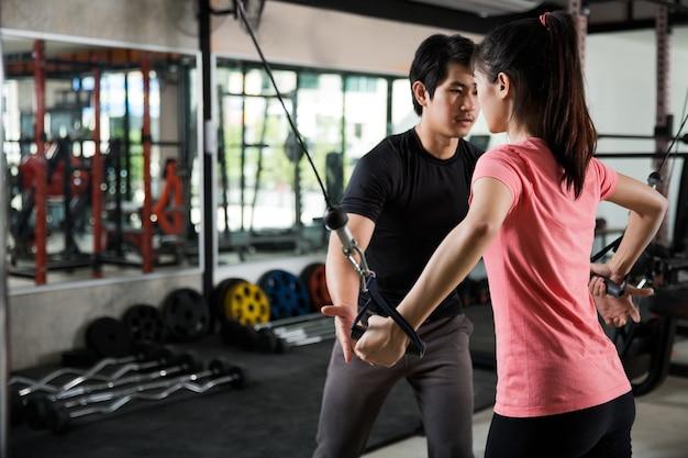 アジア人女性を教えるトレーナーの男ジムの運動は適切に
