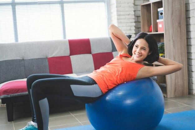アジアの女性彼女はボールを使ったエクササイズ
