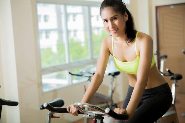 Женщина занимается в тренажерном зале на велосипеде