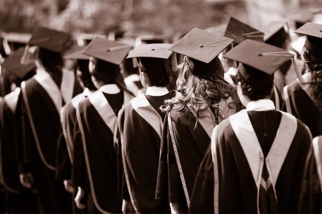 卒業生は学位を取得するために並んで歩いています