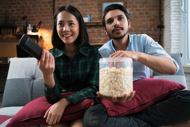 家で幸せに映画を見ているカップル。