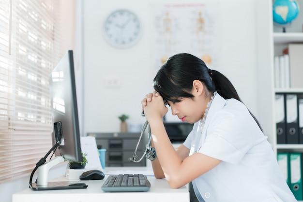 医者は診察室で休んでいます彼女は頭痛とストレスを感じています。