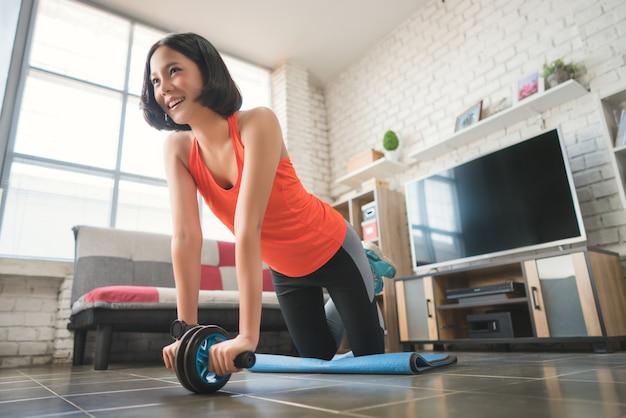 アジア人女性自宅で運動し、ローラースライドで腹筋を強化しましょう。