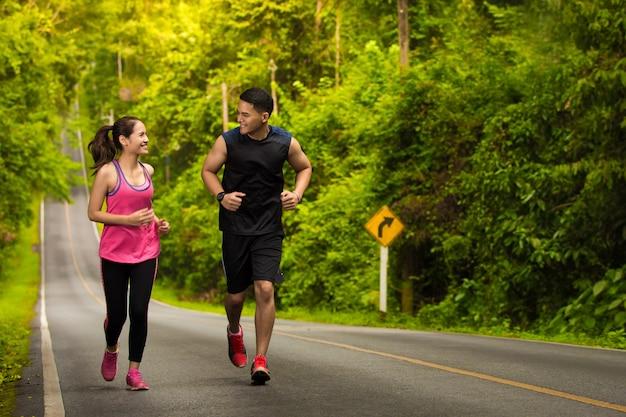ランナーのカップルが森の中の道を走って