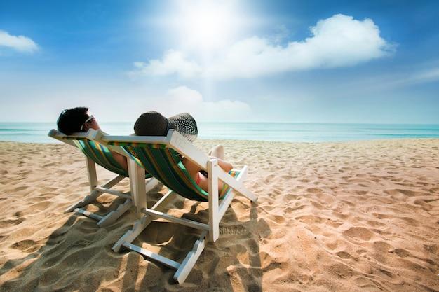 カップルのビーチチェアと傘で日光浴