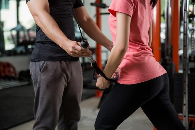 トレーナーの男性はアジアの女性のジムのエクササイズを適切に教えています