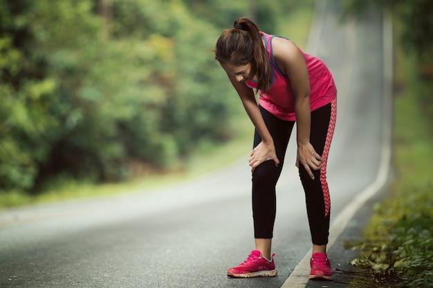 女性は急な斜面でのジョギングから疲れている