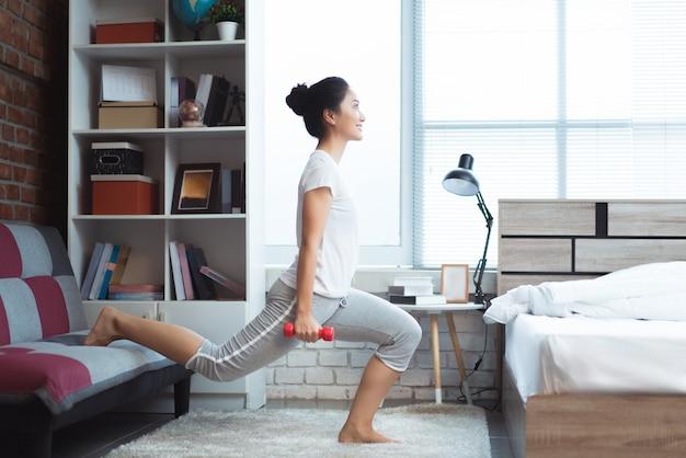 アジアの女性は午前中にベッドで運動して、彼女はさわやかに感じます。彼女はスカッシュのように振舞います。