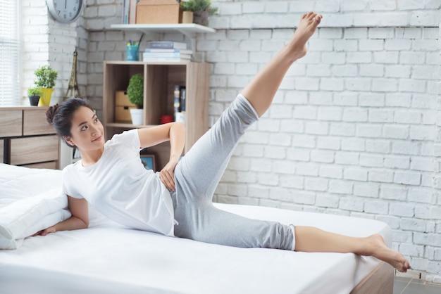 アジアの女性は午前中にベッドで運動して、彼女はさわやかに感じます。彼女はスクワットとして機能します。