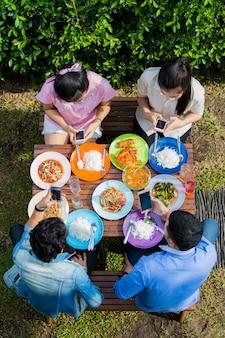 アジア人は休暇中に食べます、誰もが食べながら使うために電話を拾います