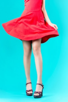 足の女性は赤いドレスを着ていて、彼女のスカートは吹きました。