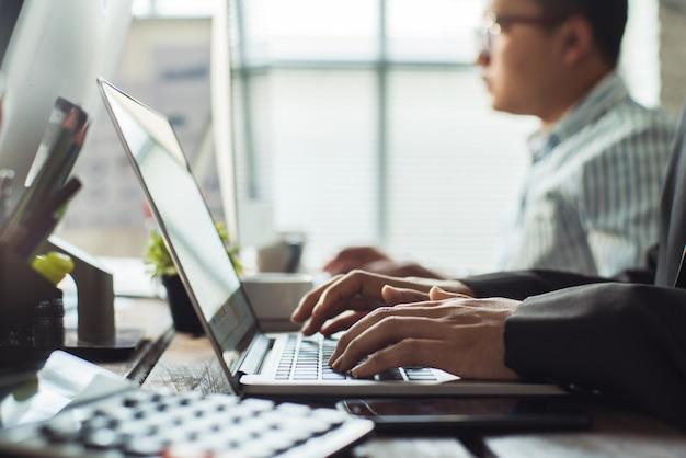 従業員の手が事務所で働いています。彼のコンピューターは財務データを入力しています。